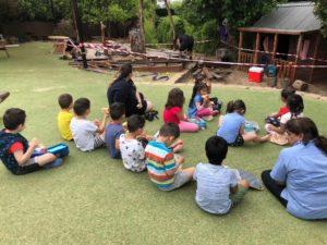 Tradie Ladies Working On Yard As Children Eat Lunch At Children First